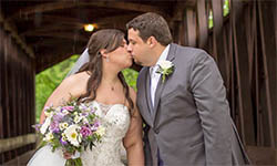 Miranda Brown kisses her husband Andrew on their wedding day as they stand on a bridge