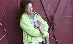 Cokie Berenyi cuddles a goat in front of a red barn door