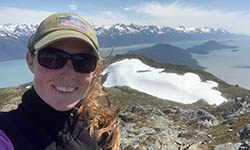 Lucy Boyce hiking in Alaska with snow covered mountains and water in the background
