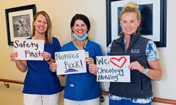 Nurses hold up signs that say safety first, nurses rock and we love oncology nursing