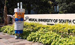 college of pharmacy's pill bottle-shaped mascot stands outside and waves next to MUSC sign