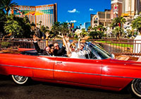 Jennifer and Mike Attisano and others in a red convertible with Las Vegas skyline in background